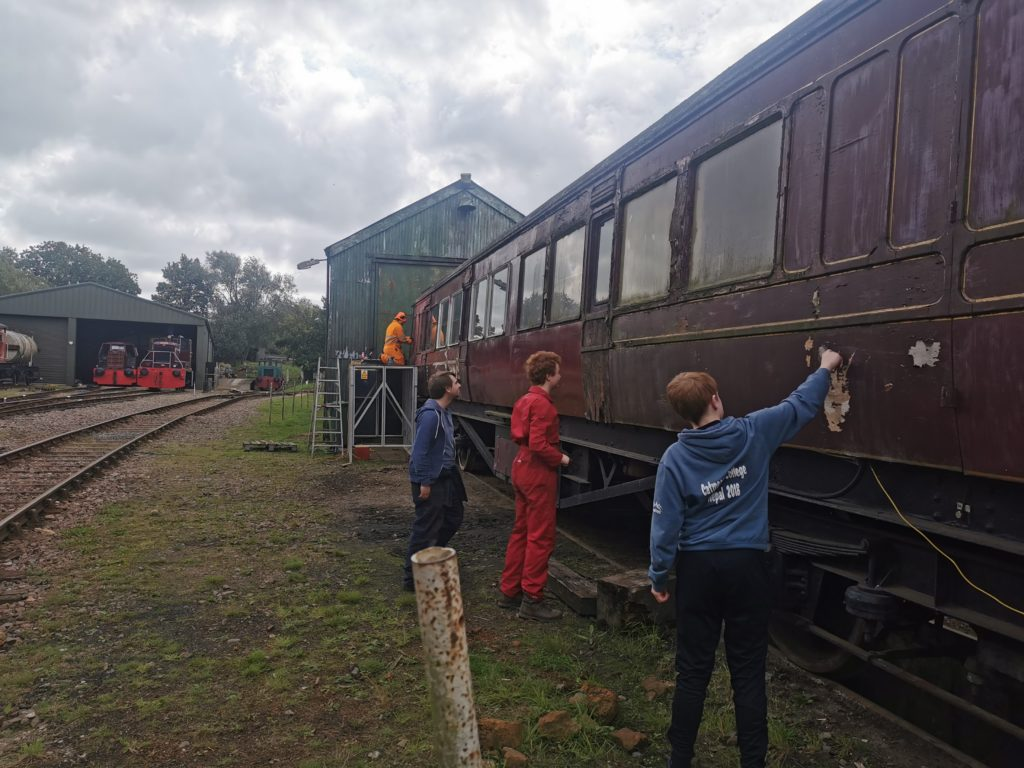 Working Day Team cleaning and sanding the coach